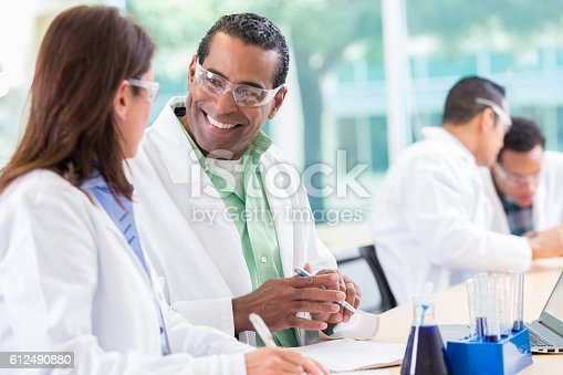 istock Cheerful experienced scientist talks with colleague 612490880