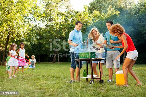 518064982 istock photo Cheerful Families barbecue outdoors. 172418390