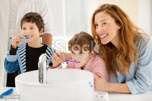 185211538istockphoto Cheerful family brushing teeth in bathroom. 453312483