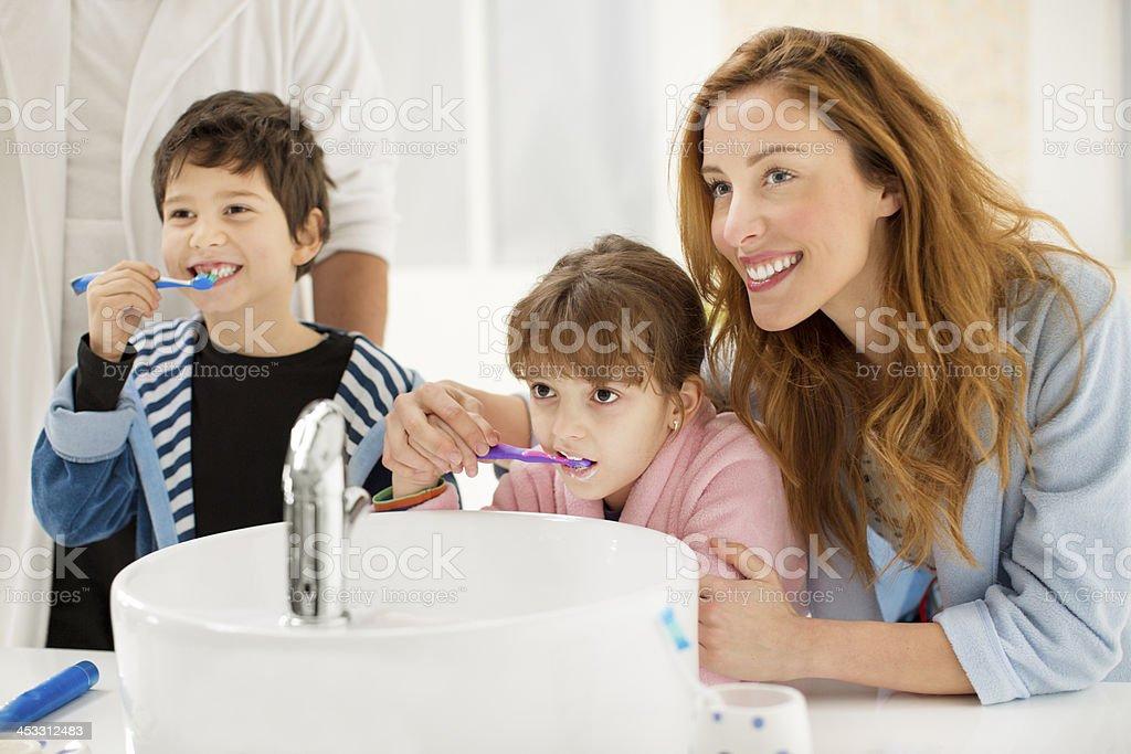 Cheerful family brushing teeth in bathroom. stock photo