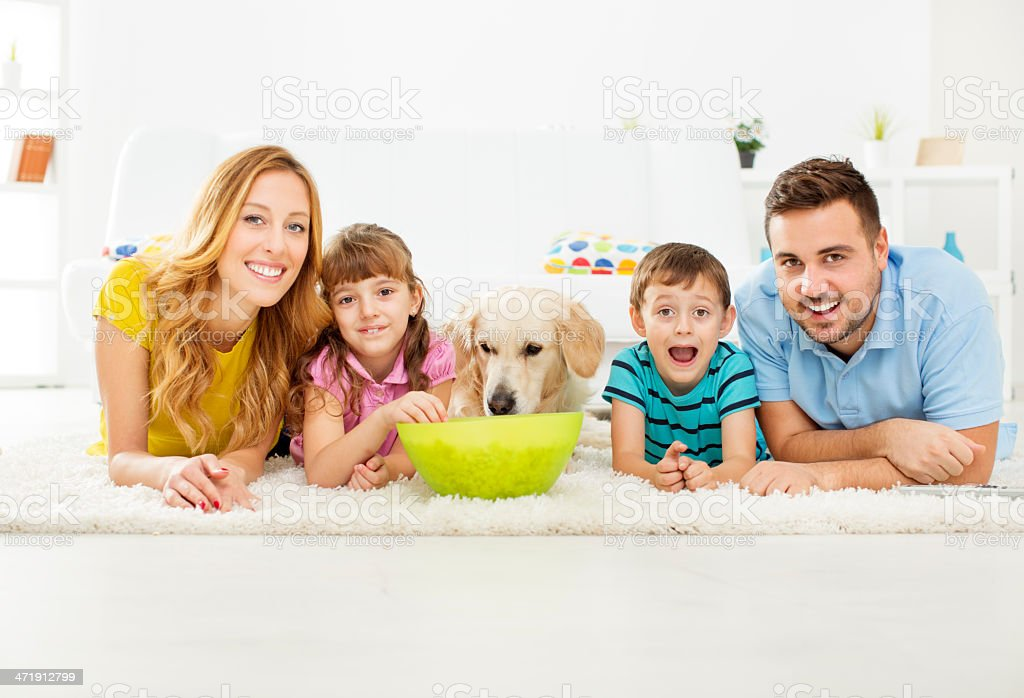 Cheerful family eating popcorns and watching TV stock photo