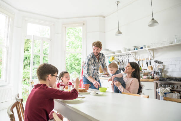 Cheerful family in kitchen having breakfast, mother holding baby and smiling stock photo