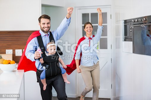 516318379istockphoto Cheerful family in superhero costume with baby 674430994