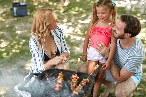cheerful family of three making barbeque outdoor