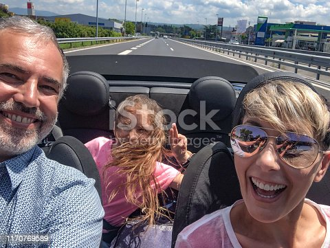 807410214istockphoto Cheerful Family on Road Trip in Covertible Car 1170769589