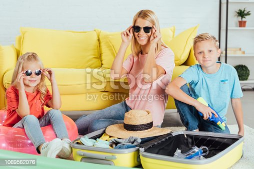 cheerful family packing baggage for for summer vacation, having fun and trying on glasses, travel concept