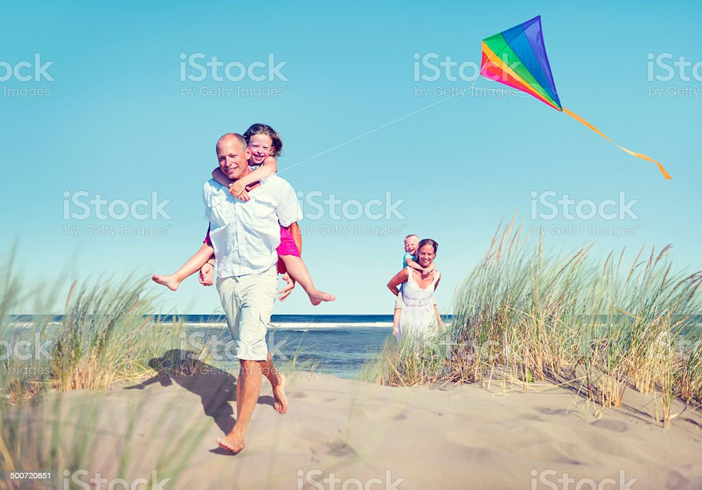 Cheerful Family Playing by the Beach stock photo