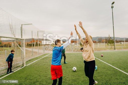 829627936 istock photo Cheerful family playing soccer together 1214759860