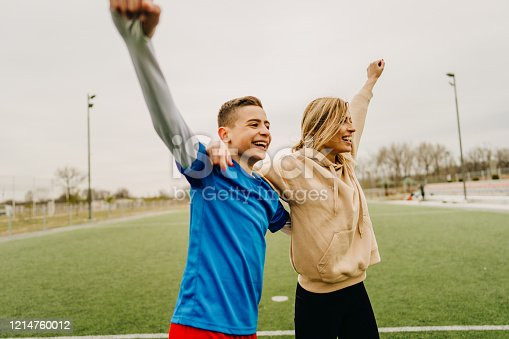 Photo of cheerful mother and son on a soccer field