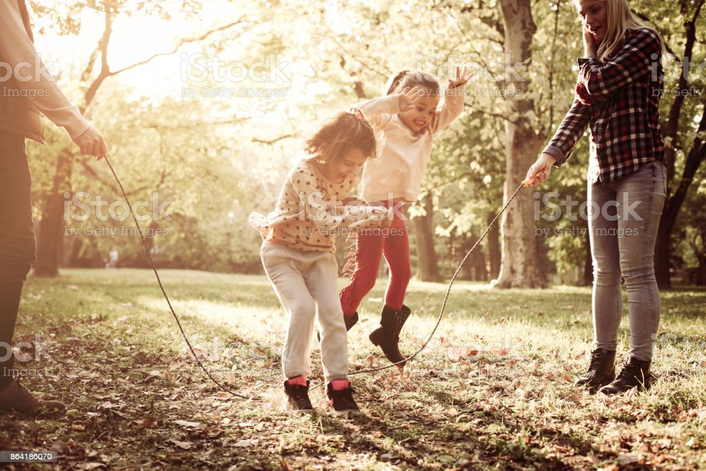 Cheerful family playing with jump rope together in park. royalty-free stock photo