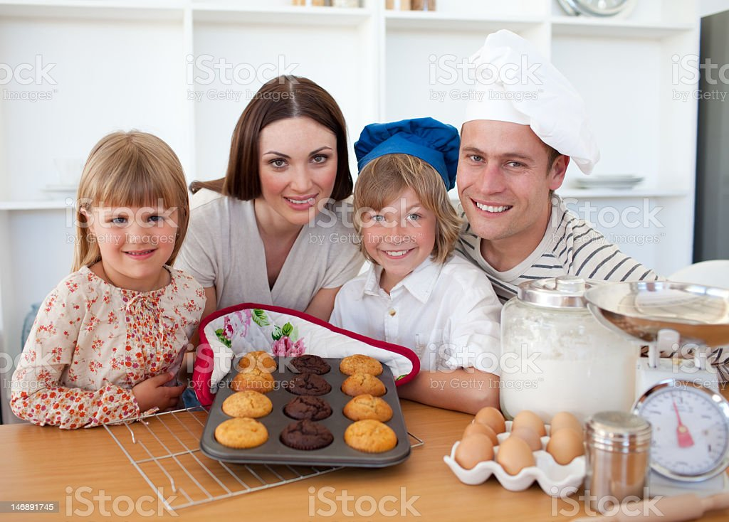 Cheerful family presenting their muffins royalty-free stock photo
