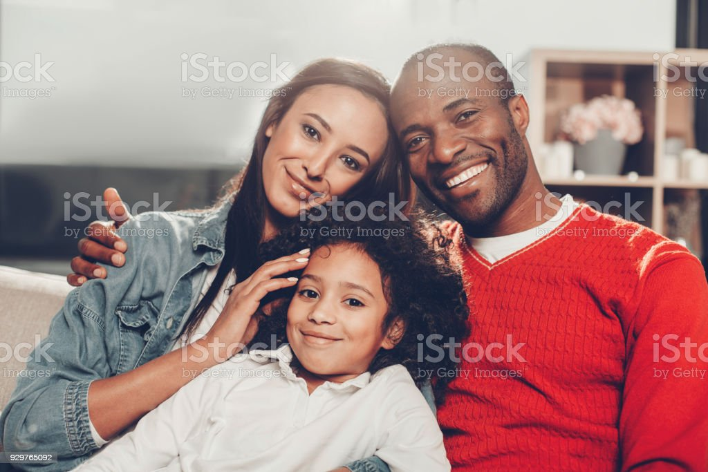 Cheerful family resting with comfort indoors stock photo