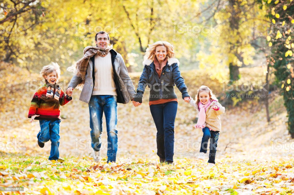 Cheerful family running in park. royalty-free stock photo