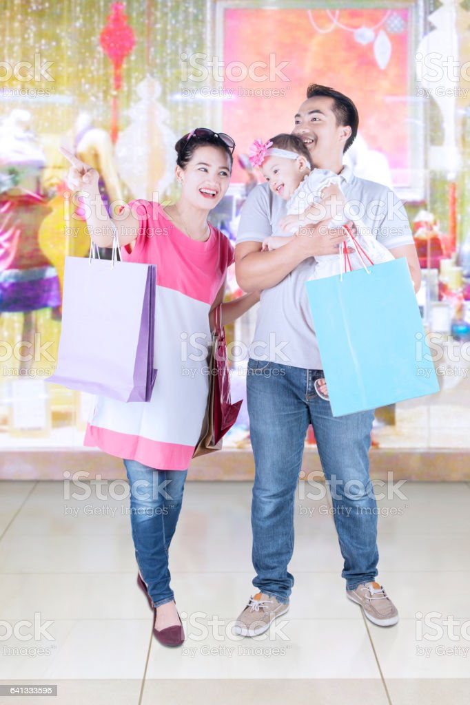 Cheerful family standing in fashion store stock photo