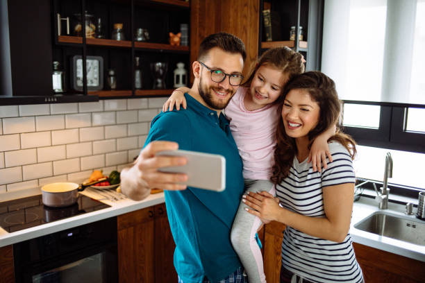 Cheerful family taking Selfie during breakfast at home stock photo