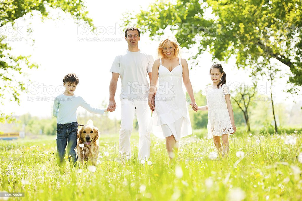 Cheerful family walking their dog in a park. royalty-free stock photo