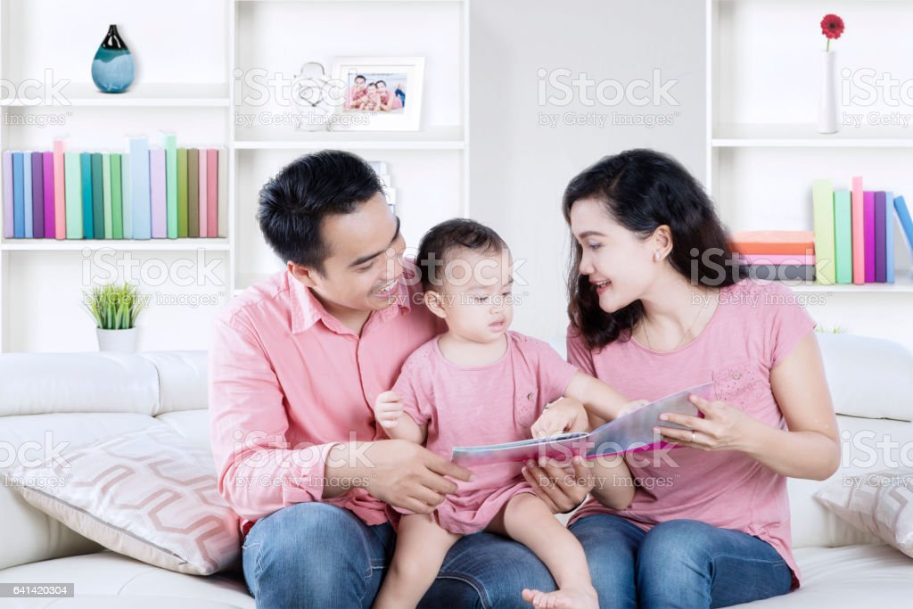 Cheerful Family With Book In Living Room Stock Photo & More Pictures ...