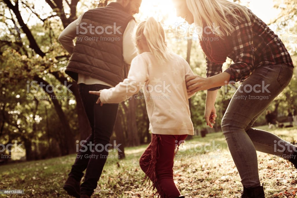 Cheerful family with one child playing together in park. royalty-free stock photo