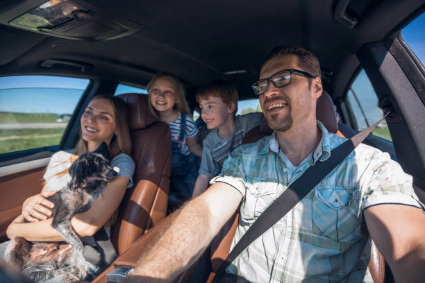 cheerful family with two children goes to the car stock photo