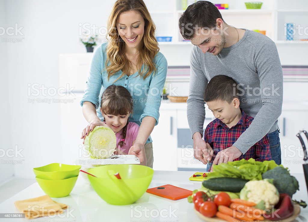 Cheerful Family With Two Children in a Kitchen. stock photo