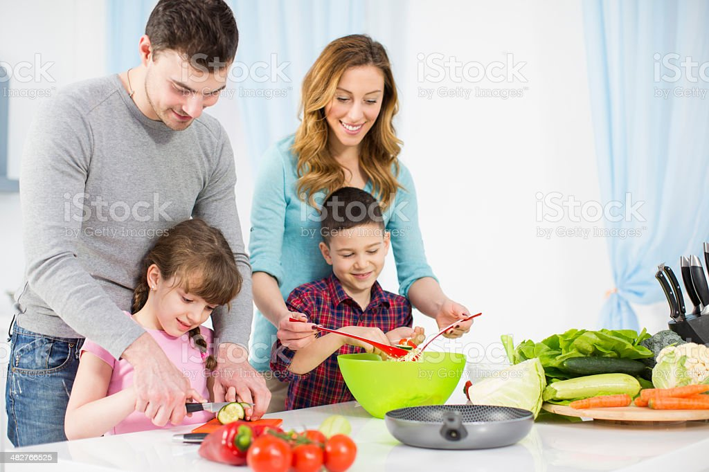 Cheerful family with two children in a kitchen royalty-free stock photo
