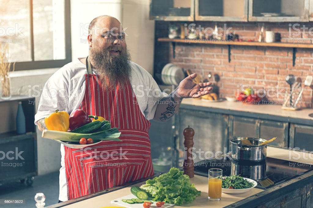 Cheerful fat guy cooking healthy food stock photo