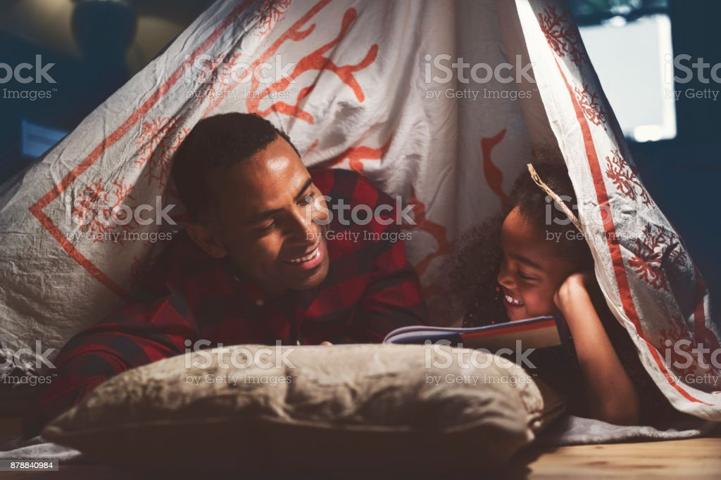 Cheerful father and daughter camping at home stock photo