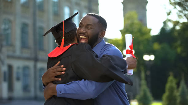 Cheerful father and graduating son hugging outdoor, study achievement, education stock photo