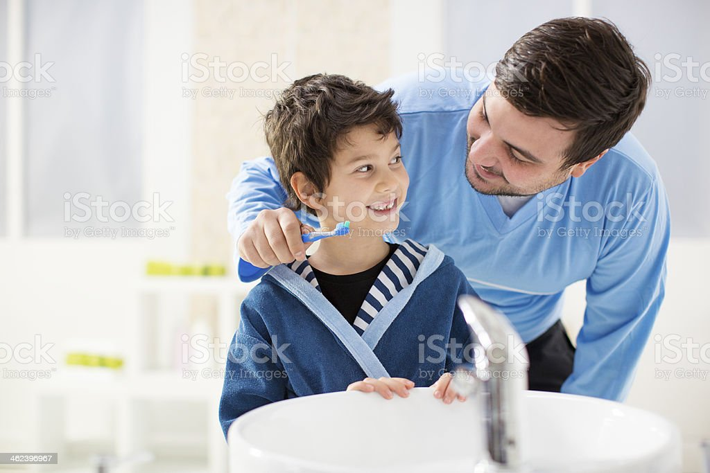 Cheerful father and son brushing teeth in bathroom. stock photo