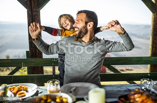Cheerful father having fun with his small son after lunch on a balcony.