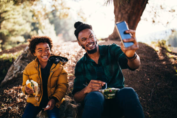 cheerful father and son taking selfies and eating in nature - eating technology stock photos and pictures