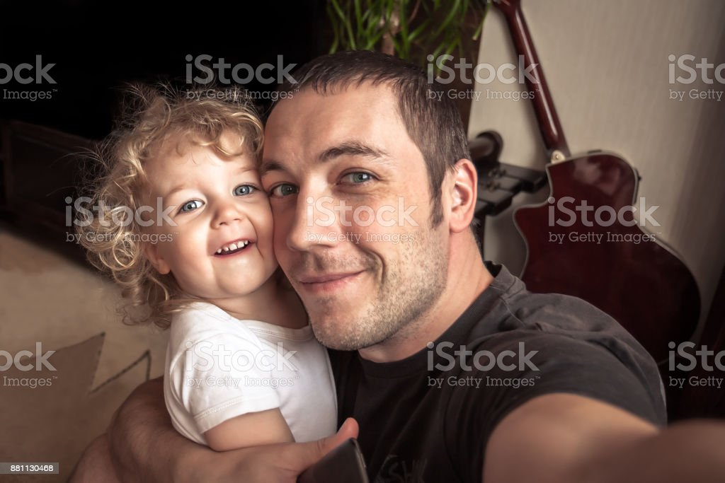 Cheerful father embracing daughter making family selfie royalty-free stock photo