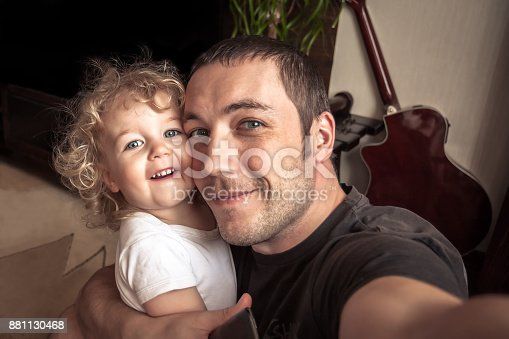 Happy father embracing daughter making family selfie