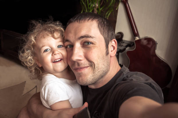 Cheerful father embracing daughter making family selfie stock photo