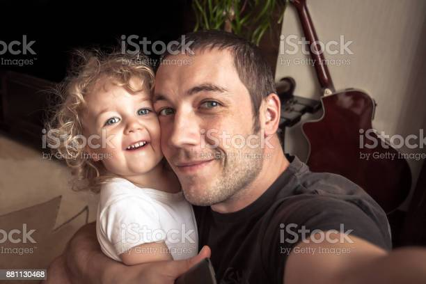 Cheerful Father Embracing Daughter Making Family Selfie Stock Photo - Download Image Now