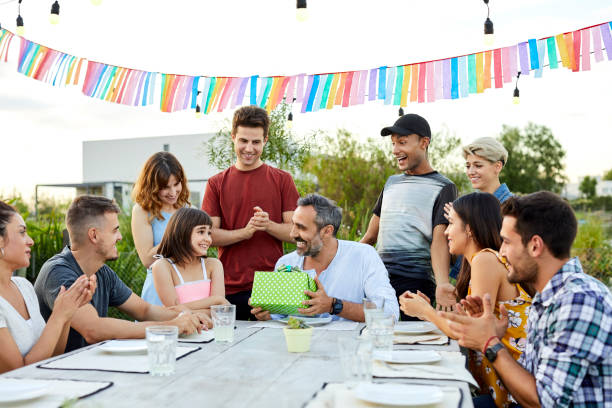 Cheerful father giving gift to daughter in yard Happy father giving birthday gift to daughter. Males and females are applauding at table. They are celebrating in backyard. group of friends giving gifts to the birthday girl stock pictures, royalty-free photos & images