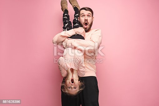 istock cheerful father playing with daughter on pink 881628396