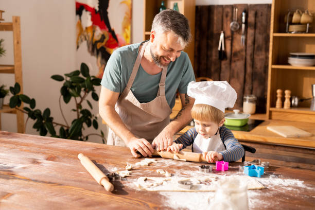 Fröhliche Vater Sohn zu Rollen Teig Lehre – Foto