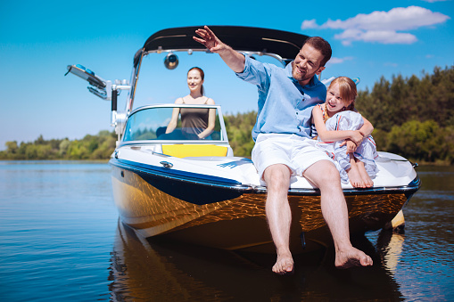 Interesting stories. Cheerful young father pointing at riverbanks and telling his little daughter stories while they sitting on the bow of the boat