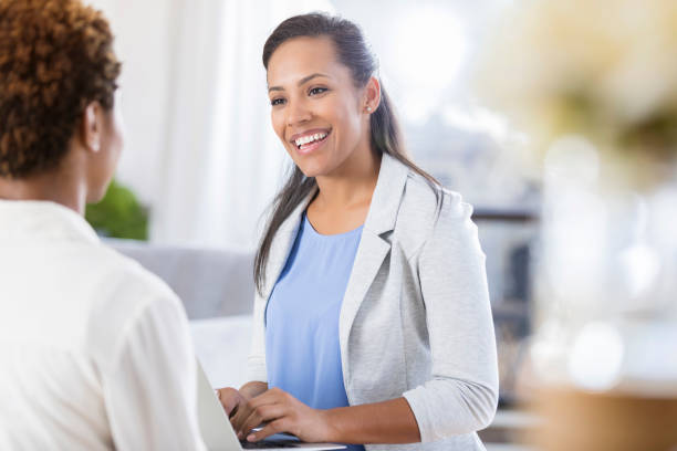 Cheerful female accountant uses laptop while meeting with client stock photo
