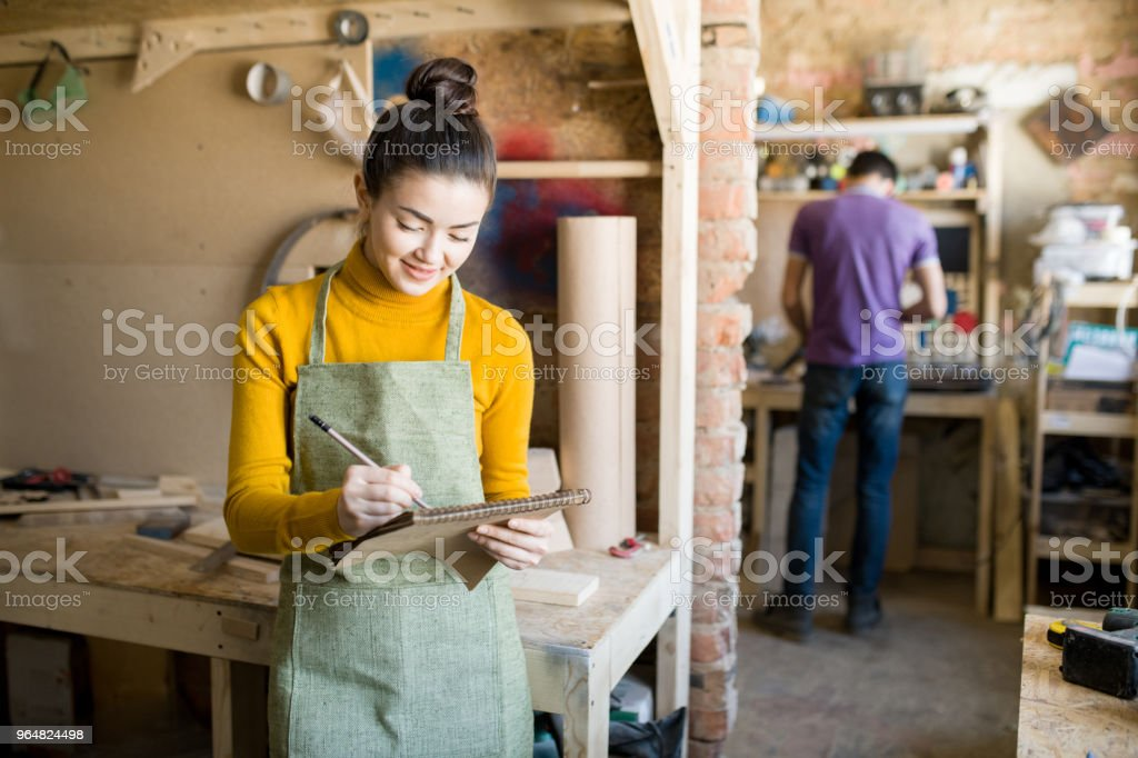 Cheerful Female Artisan in Workshop royalty-free stock photo