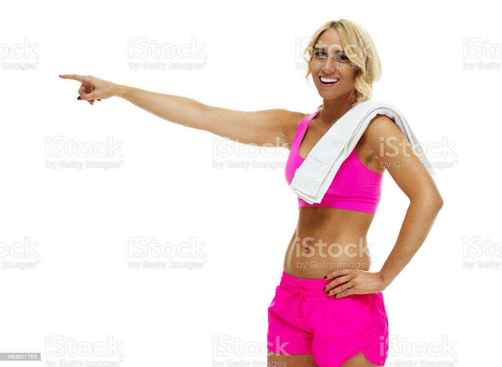 Cheerful female athlete pointing away royaltyfri bildbanksbilder