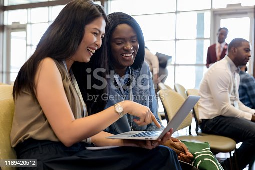 Diverse businesswomen laugh together while using a laptop during a business conference or seminar.