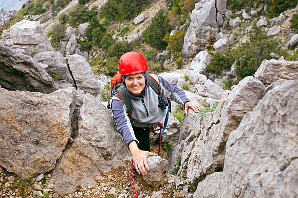 Cheerful female climber ascending a rock stock photo