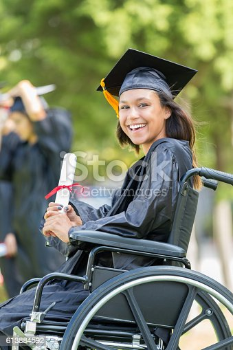 istock Cheerful female college grad with diploma 613884592