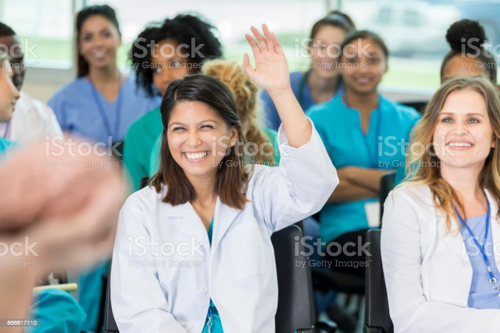 Cheerful female doctor asks question at medical seminar stock photo