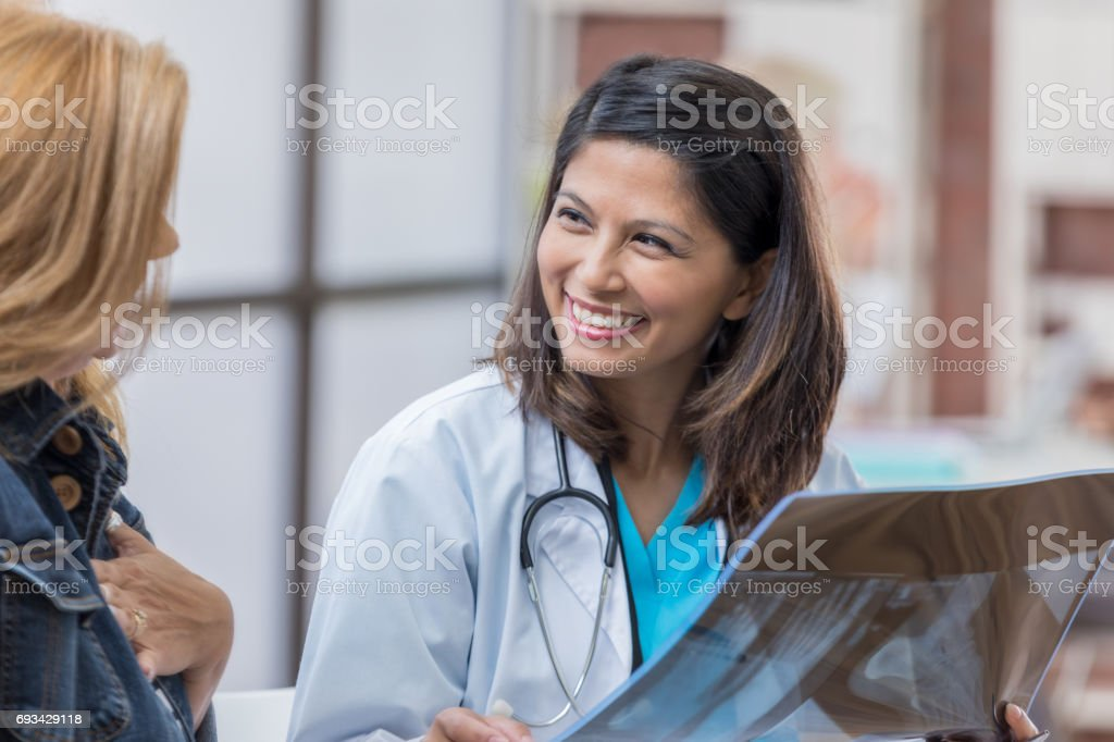 Cheerful female doctor discusses x-ray with patient stock photo