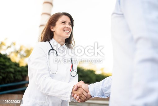 Happy female doctor shaking hands with businessman / patient outside of hospital.