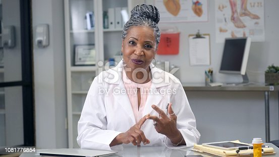 A cheerful senior female doctor sits behind a desk in her office and counts on her fingers as she explains a concept during a web conference.