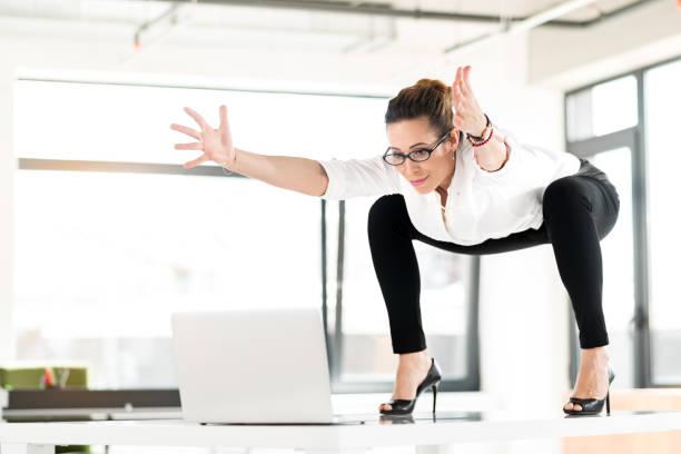 fröhliche weiblich turnen in job - yoga fürs büro stock-fotos und bilder